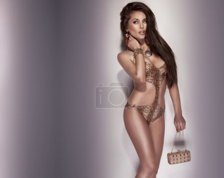Photo of sensual brunette lady with little bag.
