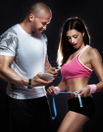 Picture of sporty woman measuring her body at the gym.