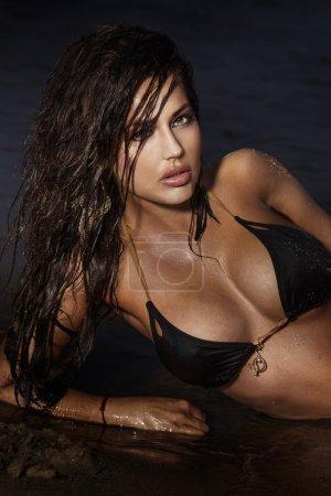 Photo pour Portrait de belle jeune femme brune allongée sur la mer, posant, regardant la caméra . - image libre de droit