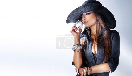 Photo pour Portrait de belle jeune femme portant un chapeau, sentant le parfum . - image libre de droit