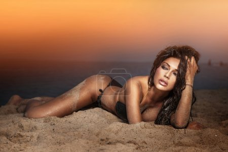 Photo for Elegant lady with perfect body laying at the beach. Evening photo during sunset. - Royalty Free Image