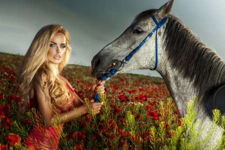 Attractive blonde woman posing with horse