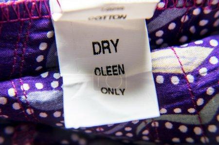 Photo pour Tissu ayant une étiquette mal pour elle de nettoyage à sec. balise de coton avec des instructions. - image libre de droit
