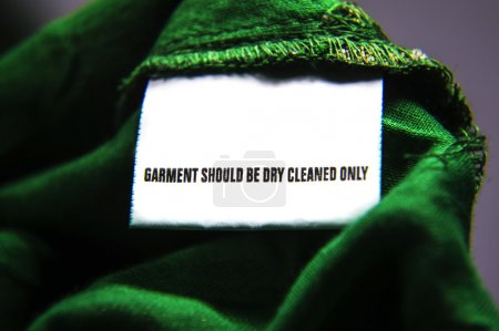 Photo for Dry clean only instructions for cloth washing. White tag on the cloth. - Royalty Free Image