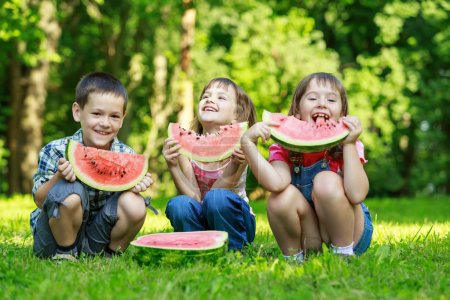 Happy smiling children eating fruits in park