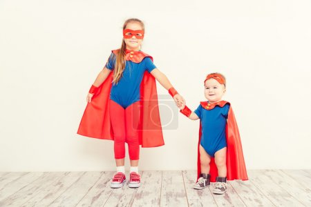 Photo pour Deux drôles de petits enfants super héros dans un imperméable rouge . - image libre de droit