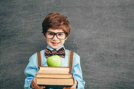 Photo pour Joyeux sourire de petit garçon avec des livres et apple contre le tableau noir. regardant la caméra. concept d'école - image libre de droit