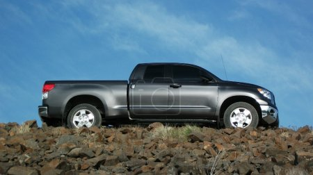 Gray pickup truck on a rock road.