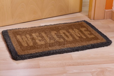 Welcome home on brown mat...
