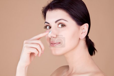 Girl touching her nose with cream (profile) on a beige background