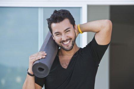 Portrait of a man holding yoga mat
