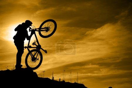 Mountain biker with bike over dramatic sky