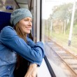 Young woman traveling by train looking out of window