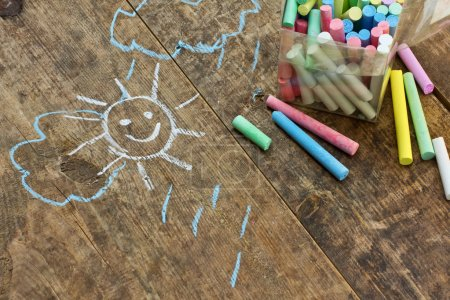 Photo for Child's drawings and coloured chalk on wooden background - Royalty Free Image