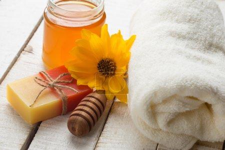 Photo pour Concept de Spa. spa de miel. barre de serviette à la main, naturel, miel et fleur sur fond en bois. mise au point sélective. - image libre de droit