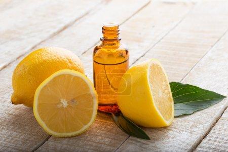 Photo pour Huile essentielle d'arôme avec des citrons sur fond bois. Concentration sélective . - image libre de droit