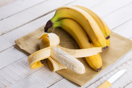 Photo for Fresh bananas on towel on white wooden background. Selective focus. - Royalty Free Image