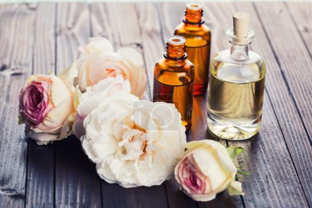 Photo for Essential aroma oil with roses on wooden background - Royalty Free Image