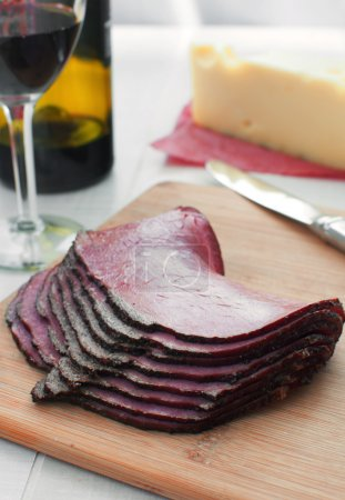 Photo for Thin sliced deli pastrami meat with cheese and wine - Royalty Free Image