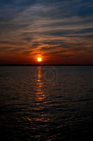 Photo for Dramatic orange sunset on dark sky with clouds vertical - Royalty Free Image