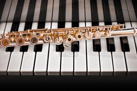 Photo pour Flûte or de 14 k rose sur une touches du piano - image libre de droit