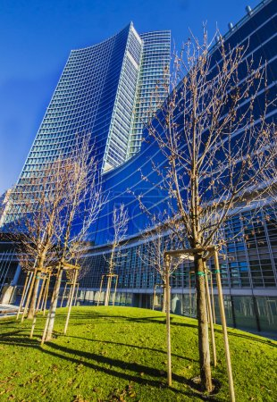Leafless trees infront of a tall building under th...