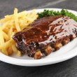 Grilled juicy barbecue pork ribs in a white plate ...