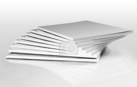 Foto de Pila de revistas con una funda en blanco, aislado en blanco - Imagen libre de derechos