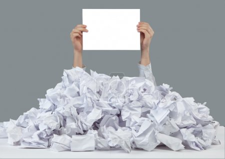 Photo for Hands with empty paper reaches out from big heap of crumpled papers - Royalty Free Image