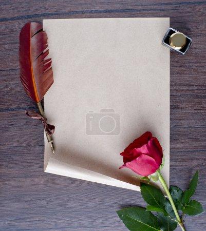 Photo pour Stylo et du papier ancien avec une rose sur une table en bois - image libre de droit