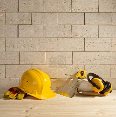 Photo pour Fond en brique beige, casque jaune et truelle sur un plancher en bois - image libre de droit