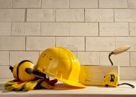 brick background, helmet and measuring tape