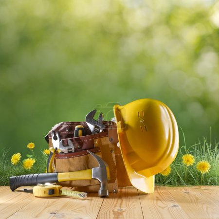 Photo for Construction tool and helmet on green nature background - Royalty Free Image
