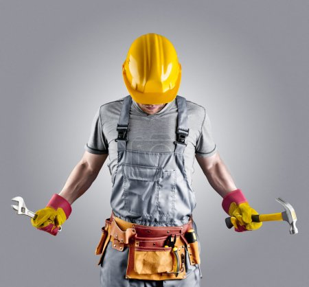 builder in a helmet with a hammer and a wrench