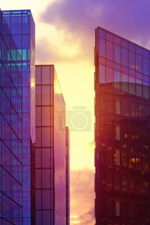 Modern glass buildings in London at purple sunset