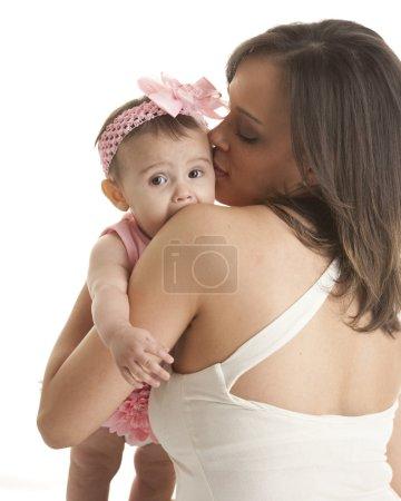 Mother hugging her teething baby daughter