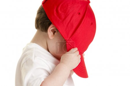 Little boy pulling a ball cap down over his face