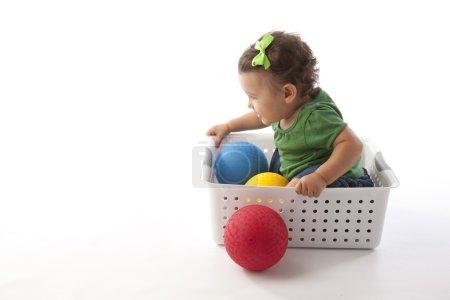 Сute baby girl posing in a basket