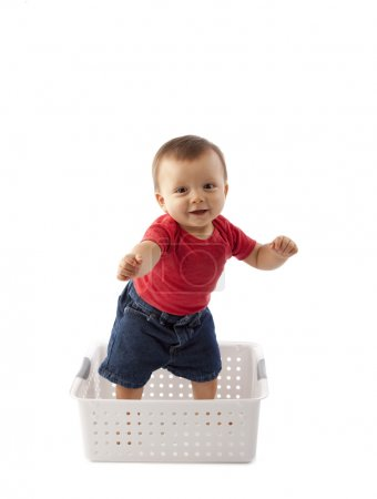 Baby boy standing precariously in a bacsket