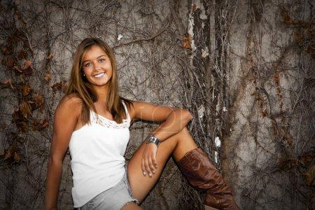 Beautiful teenage girl wearing a cut off denim shorts and cowboy boots