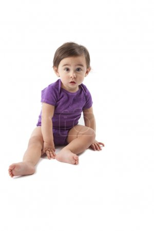 Cute baby girl wearing T-shirt sitting on the floor