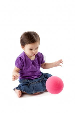 Baby girl bouncing and playing with ball