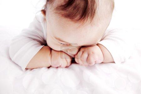 Photo pour Bébé de cinq mois, la tête baissée et les yeux frottés comme s'il était endormi - image libre de droit