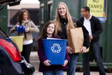 Volunteer employee helping girls at recycling center