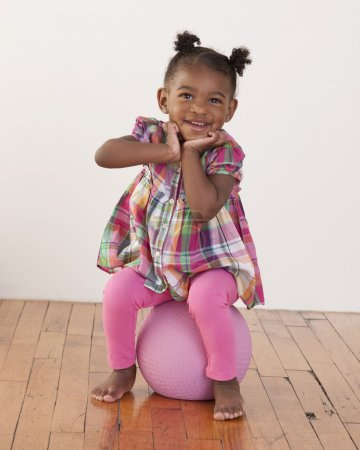 Headshot of toddler girl sitting on a ball