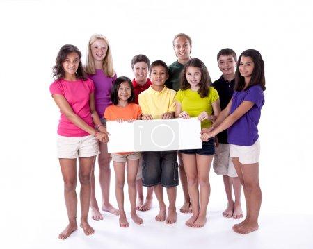 Photo pour Un groupe diversifié de neuf enfants et adolescents de différentes ethnies et races se sont réunis en tenant un signe blanc vierge - image libre de droit