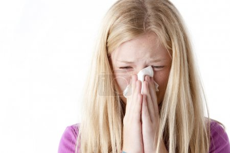 Blonde girl wiping her nose with a tissue