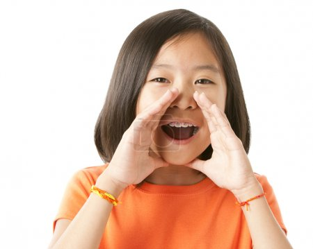 Photo for A nine-year old asian girl holding her hands to her mouth and yelling or cheers - Royalty Free Image