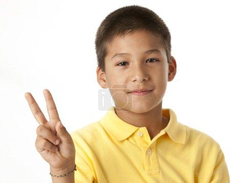 Cute hispanic boy giving a peace sign
