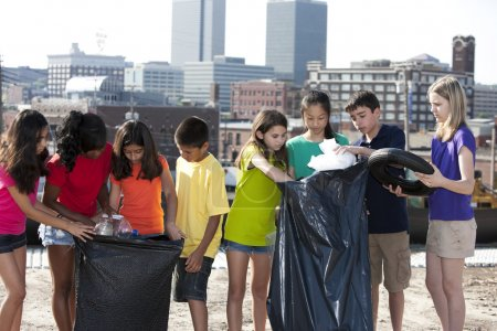 Group of children of different ethnicities picking up trash in an urban area
